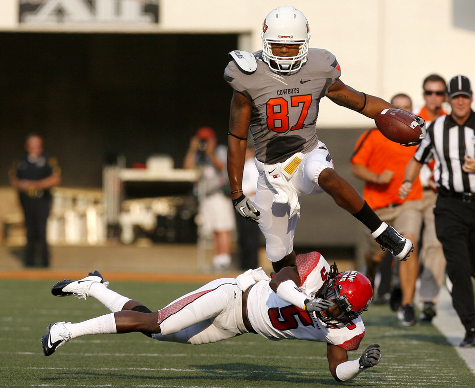 Photo - Oklahoma State's Tracy Moore leaps over Louisiana-Lafayette's Dwight Bentley (5) during Saturday's game in Stillwater. Photo by Sarah Phipps, The Oklahoman