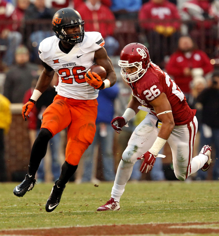 Photo - Cowboy's Desmond Roland (26) is pursued by Sooner Jordan Evans (26) during a Bedlam college football game between the University of Oklahoma Sooners (OU) and the Oklahoma State Cowboys (OSU) at Gaylord Family-Oklahoma Memorial Stadium in Norman, Okla., on Saturday, Dec. 6, 2014. Photo by Steve Sisney, The Oklahoman