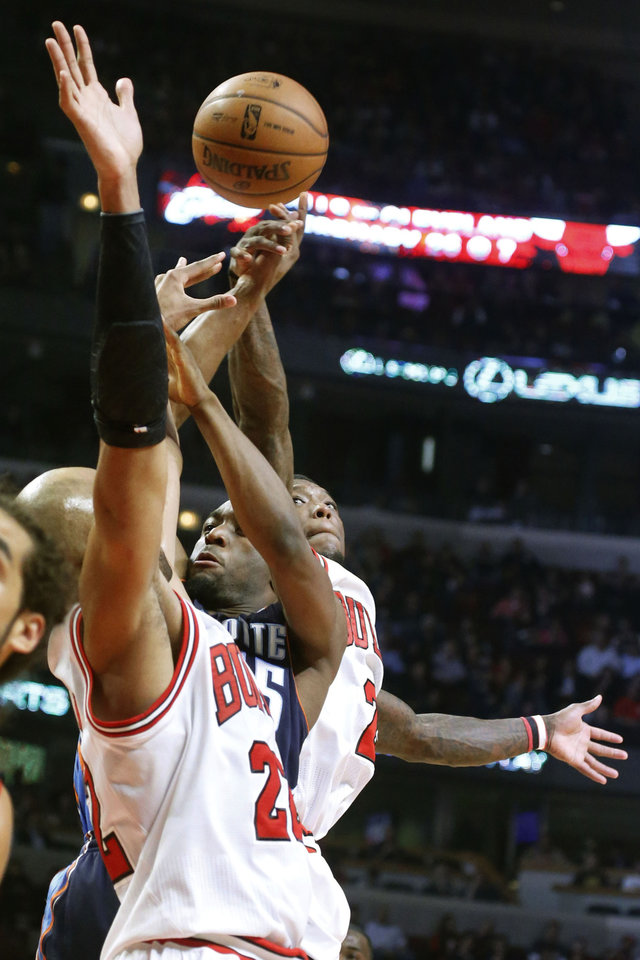 Charlotte Bobcats guard Kemba Walker, center, has his shot blocked from behind by Chicago Bulls guard Nate Robinson as Taj Gibson defends during the first half of an NBA basketball game, Monday, Jan. 28, 2013, in Chicago. (AP Photo/Charles Rex Arbogast)