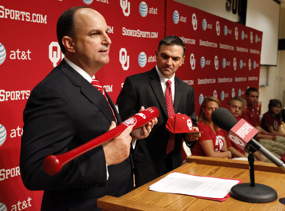 Photo - Athletics Director Joe Castiglione hands Pete Hughes a commemorative bat and OU hat as he is introduced as the University of Oklahoma (OU) Sooners new baseball coach on Thursday, June 27, 2013 in Norman, Okla. Photo by Steve Sisney, The Oklahoman