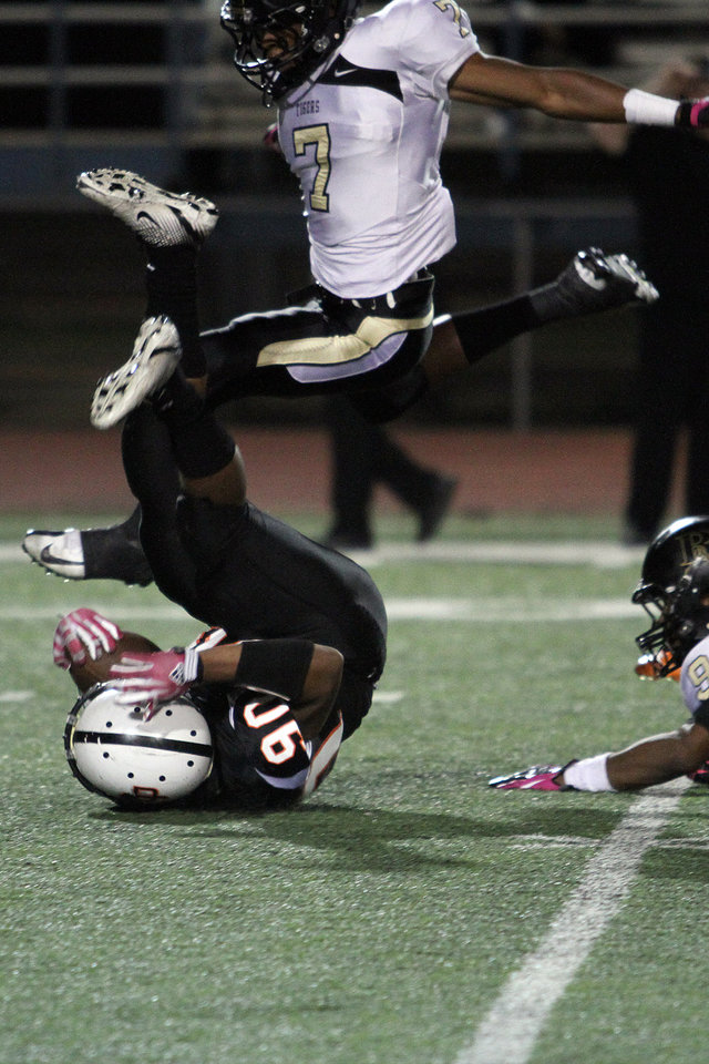 Photo - Putnam City's BJ Tomlin is upended after a 24 yard run as Broken Arrow's Cre Moore jumps over during Putnam City - Broken Arrow high school football game at Putnam City Stadium Friday night. PHOTO BY HUGH SCOTT FOR THE OKLAHOMAN ORG XMIT: KOD