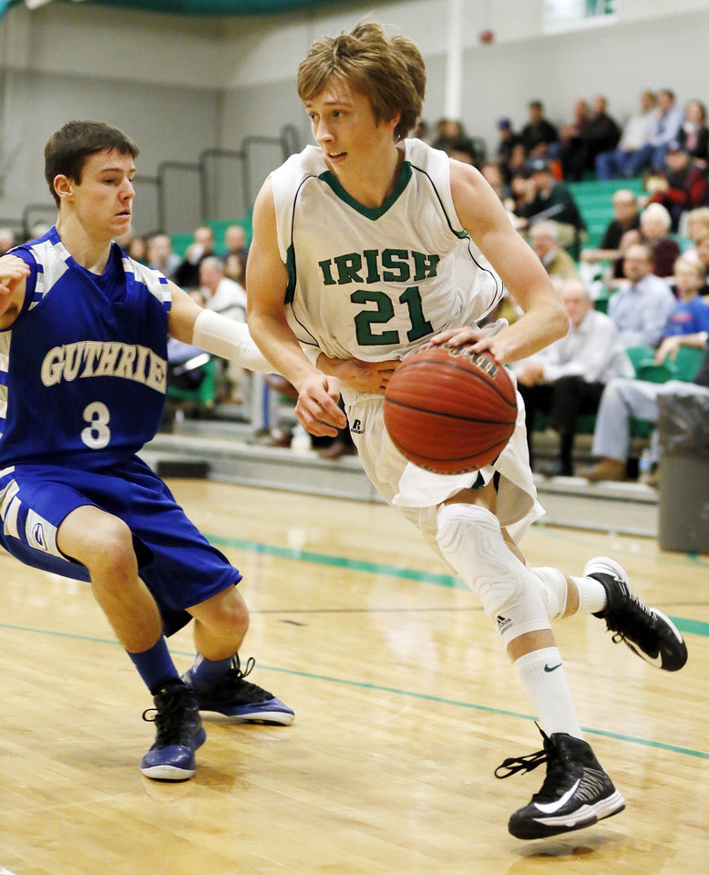 Brian Canfield (21) of Bishop McGuinness drives the ball against TJ Wilson (3) of Guthrie during a game between Guthrie and Bishop McGuinness in the McGuinness Classic boys high school basketball tournament at Bishop McGuinness Catholic High School in Oklahoma City, Friday, Jan. 11, 2013. Photo by Nate Billings, The Oklahoman
