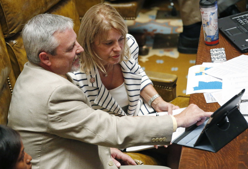 Photo - Rep. Bill Kinkade, R-Byhalia, left, helps recently elected Rep. Patricia Willis, R-Diamondhead, use the internet to track legislation during floor debate over Medicaid reauthorization Thursday afternoon, June 27, 2013 at the Capitol in Jackson, Miss. Willis is filling the remainder of the unfinished term of the late Rep. Jessica Upshaw, also a Republican from Diamondhead. (AP Photo/Rogelio V. Solis)
