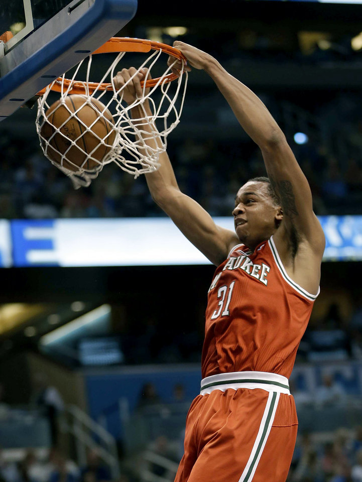 Photo - Milwaukee Bucks' John Henson (31) make an uncontested dunk against the Orlando Magic during the first half of an NBA basketball game, Wednesday, April 10, 2013, in Orlando, Fla. (AP Photo/John Raoux)