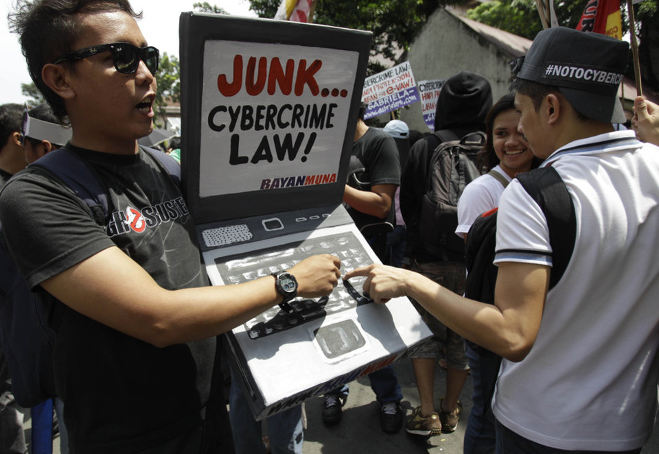 Photo -   A protester holds a mock laptop during a rally against the anti-cybercrime law in front of the Supreme Court in Manila, Philippines, Tuesday Oct. 9, 2012. The Philippine Supreme Court on Tuesday suspended implementation of the country's anti-cybercrime law while it decides whether certain provisions violate civil liberties. The law aims to combat Internet crimes such as hacking, identity theft, spamming, cybersex and online child pornography. (AP Photo/Aaron Favila)