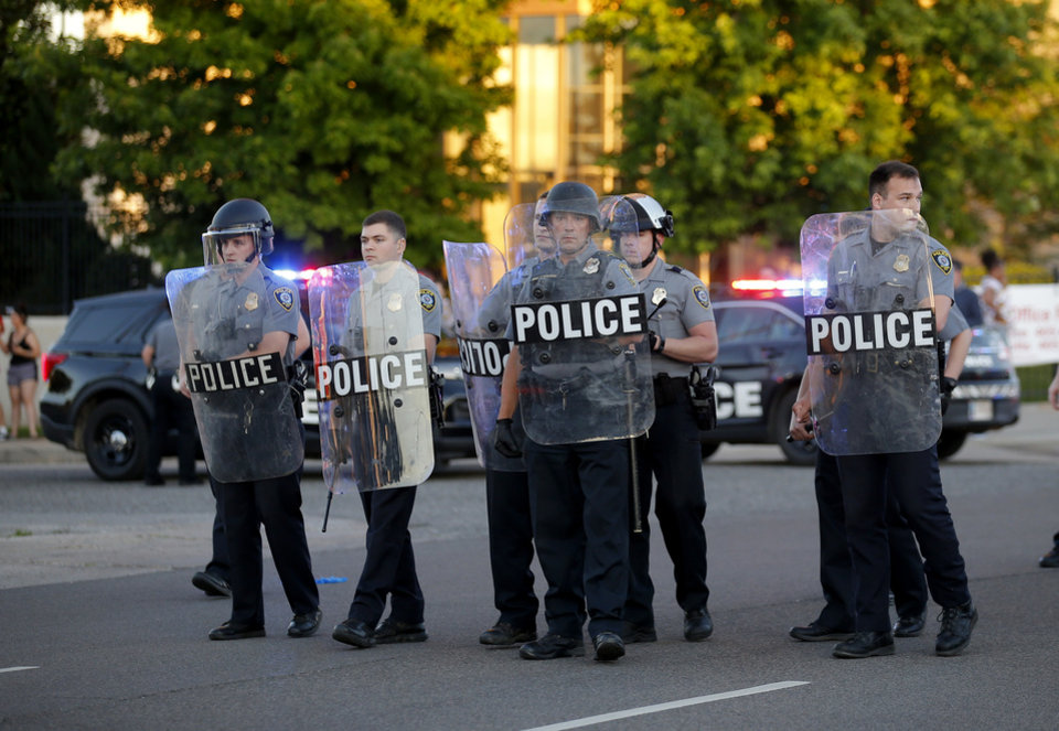 Photo - Police stand near protesters during a protest near the intersection of 23rd and Classen in Oklahoma City, Saturday, May 30, 2020. The protest was in response to the death of George Floyd. [Sarah Phipps/The Oklahoman]