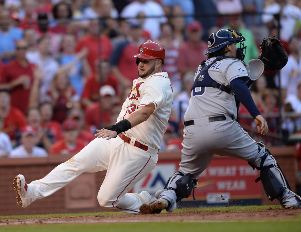 Photo - St. Louis Cardinals' Matt Adams, left, scores on a double by Jhonny Peralta as San Diego Padres' Yasmani Grandal, right, can't make the tag in the second inning in a baseball game, Saturday, Aug. 16, 2014, at Busch Stadium in St. Louis. (AP Photo/Bill Boyce)