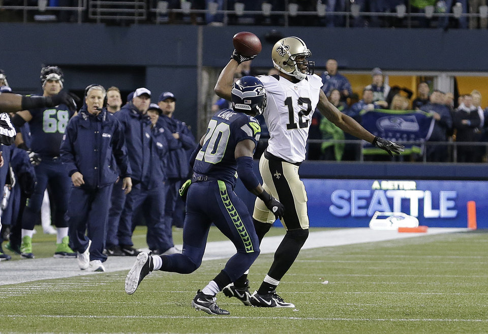 Photo - New Orleans Saints wide receiver Marques Colston (12) throws the ball after catching a pass next to Seattle Seahawks cornerback Jeremy Lane (20) during the fourth quarter of an NFC divisional playoff NFL football game in Seattle, Saturday, Jan. 11, 2014. The Seahawks won 23-15. Instead of stepping out of bounds to have one more play, Colston tried to throw across the field to Darren Sproles. The pass was forward and the penalty for an illegal forward pass ran off the final 10 seconds of the clock giving Seattle the victory. (AP Photo/Elaine Thompson)