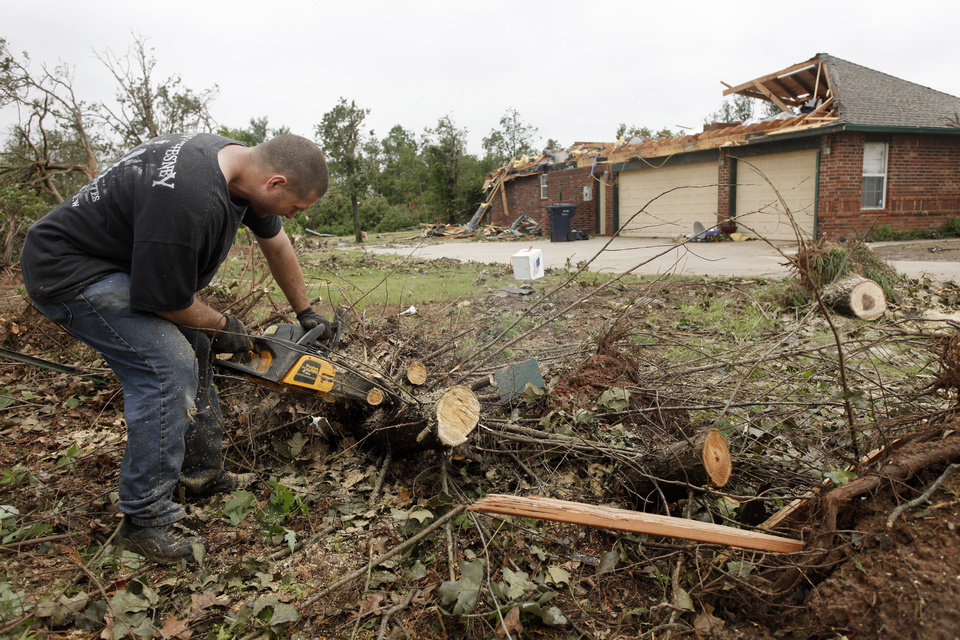 Photo - Rory Farmer cuts up damaged trees so they can be oved to the street in the Dripping Springs Estates Saturday, May 15, 2010. Saturday hundreds of volunteers went into areas that had been affected by last week's tornadoes to help clear debris. Photo by Doug Hoke, The Oklahoman.