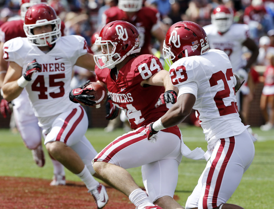 Photo - Don Caudill (84) runs between Caleb Gastelum (45) and Kass Everett (23) after a catch during the annual Spring Football Game at Gaylord Family-Oklahoma Memorial Stadium in Norman, Okla., on Saturday, April 13, 2013. Photo by Steve Sisney, The Oklahoman