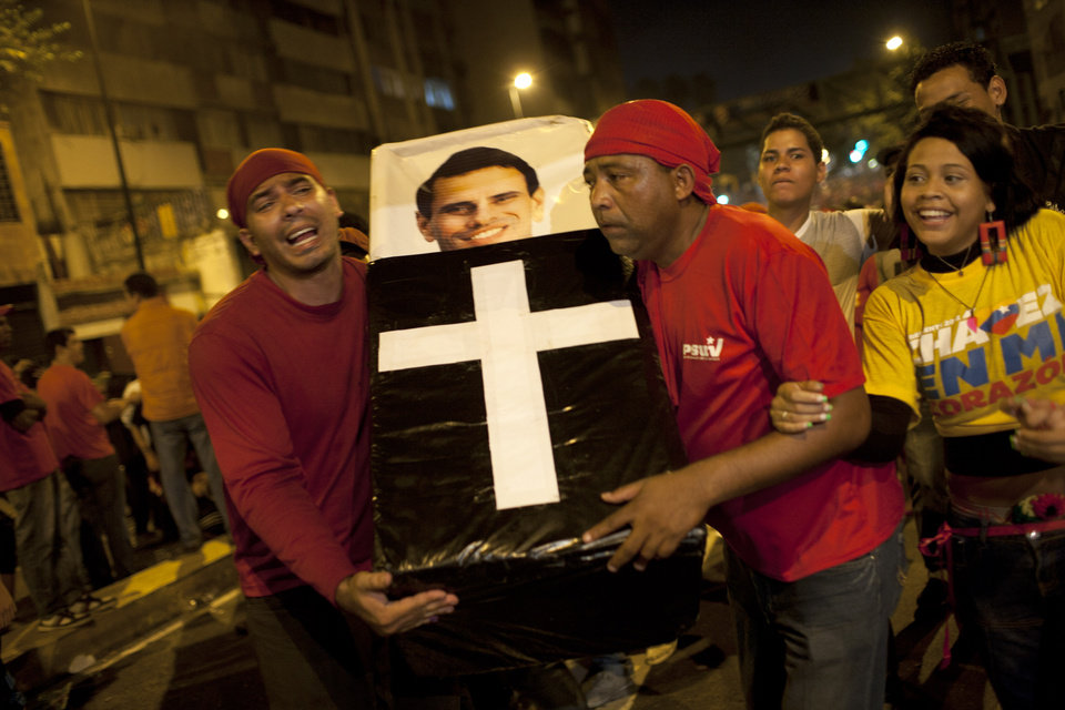 Photo -   Supporters of Venezuela's President Hugo Chavez perform a mock funeral for opposition candidate Henrique Capriles as they celebrate in downtown Caracas, Venezuela, Sunday, Oct. 7, 2012. Chavez won re-election and a new endorsement of his socialist project Sunday, surviving his closest race yet after a bitter campaign against Capriles.(AP Photo/Ariana Cubillos)