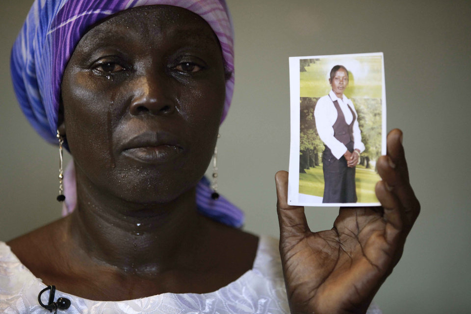 Photo - FILE-In this Monday, May 19, 2014 file photo, Martha Mark, the mother of kidnapped school girl Monica Mark cries as she displays her photo, in the family house, in Chibok, Nigeria. At least 11 parents of the more than 200 kidnapped Nigerian schoolgirls will never see their daughters again. Since the mass abduction of the schoolgirls by Islamic extremists three months ago, at least 11 of their parents have died and their hometown, Chibok, is under siege from the militants, residents report. Seven fathers of kidnapped girls were among 51 bodies brought to Chibok hospital after an attack on the nearby village of Kautakari this month, said a health worker who insisted on anonymity for fear of reprisals by the extremists. At least four more parents have died of heart failure, high blood pressure and other illnesses that the community blames on trauma due to the mass abduction 100 days ago, said community leader Pogu Bitrus, who provided their names. (AP Photo/Sunday Alamba File)