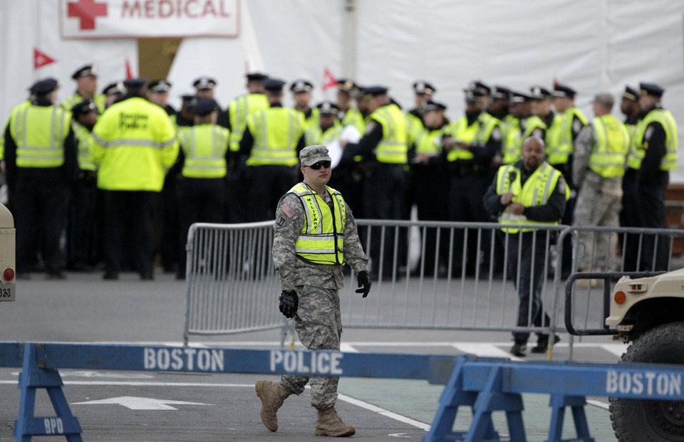 Officials congregate near the medical tent at the Boston Marathon finish line, Thursday, April 18, 2013, in Boston.  President Barack Obama plans to attend a service honoring the victims Thursday in Boston, where police were stationed on street corners across downtown.  (AP Photo/Julio Cortez)