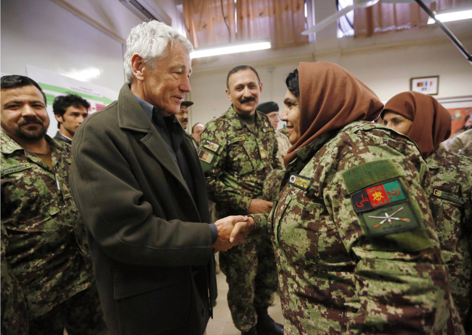 Photo - U.S. Secretary of Defense Chuck Hagel, center left, shakes hands with a female Afghan non-commissioned officer under training, during his visit to the Kabul Military Training Center in Kabul, Afghanistan, Sunday, March 10, 2013. Hagel is on his first trip to Afghanistan as defense secretary. (AP Photo/Jason Reed, Pool)