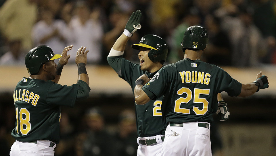 Photo - Oakland Athletics' Kurt Suzuki, center, is congratulated by Alberto Callaspo (18) and Chris Young (25) after Suzuki hit a three-run home run off Tampa Bay Rays' David Price in the fifth inning of a baseball game, Friday, Aug. 30, 2013, in Oakland, Calif. (AP Photo/Ben Margot)