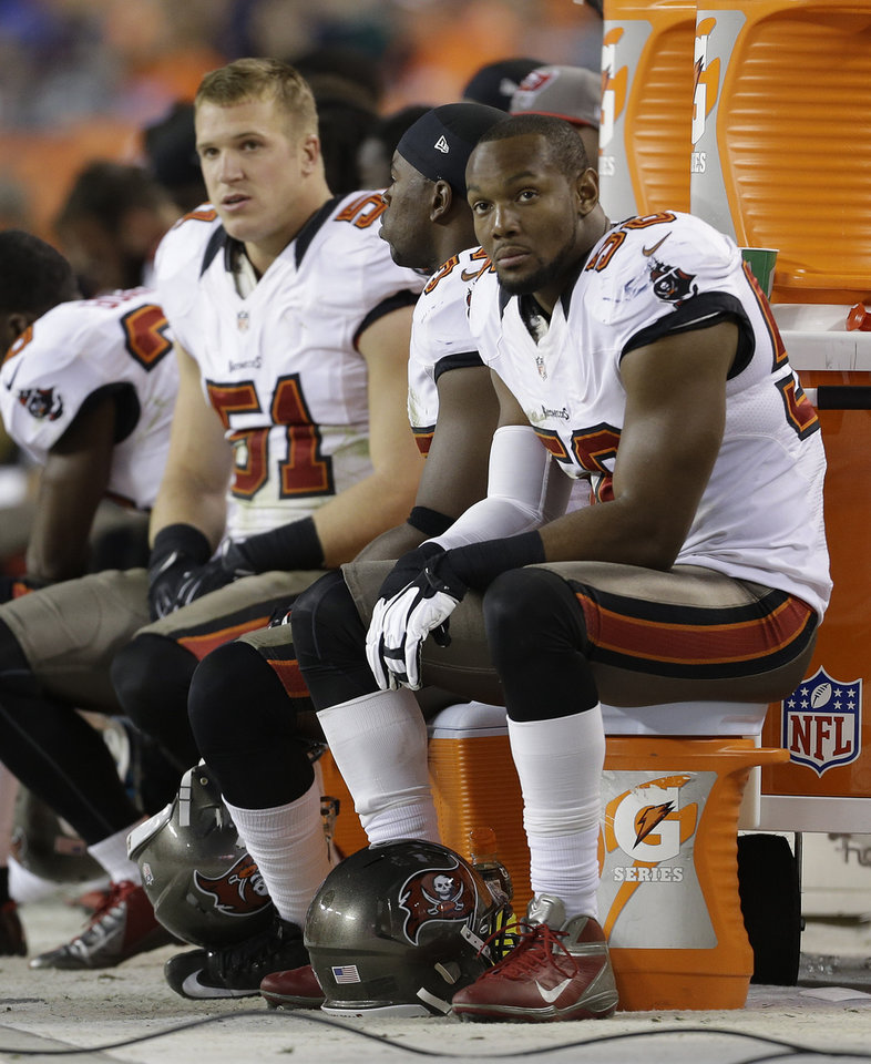 Photo - Tampa Bay Buccaneers linebacker Dekoda Watson (56) watches from the bench with linebacker Jacob Cutrera (51) in the fourth quarter of an NFL football game against the Denver Broncos, Sunday, Dec. 2, 2012, in Denver. (AP Photo/Joe Mahoney)