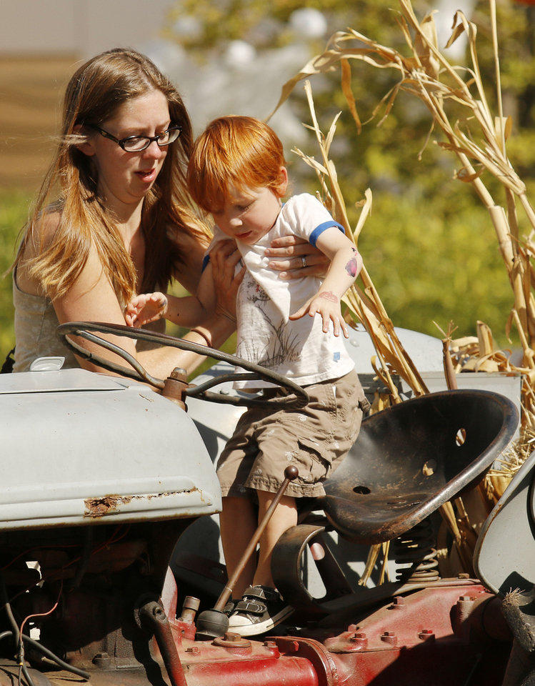 Photo - Anny Gooding-Lee helps her son Benjamin Neville-Lee, 2, get on a tractor in Pumpkinville at the Mryiad Botanical Gardens during a preview on Friday.  PHOTO BY DOUG HOKE, THE OKLAHOMAN  DOUG HOKE - THE OKLAHOMAN