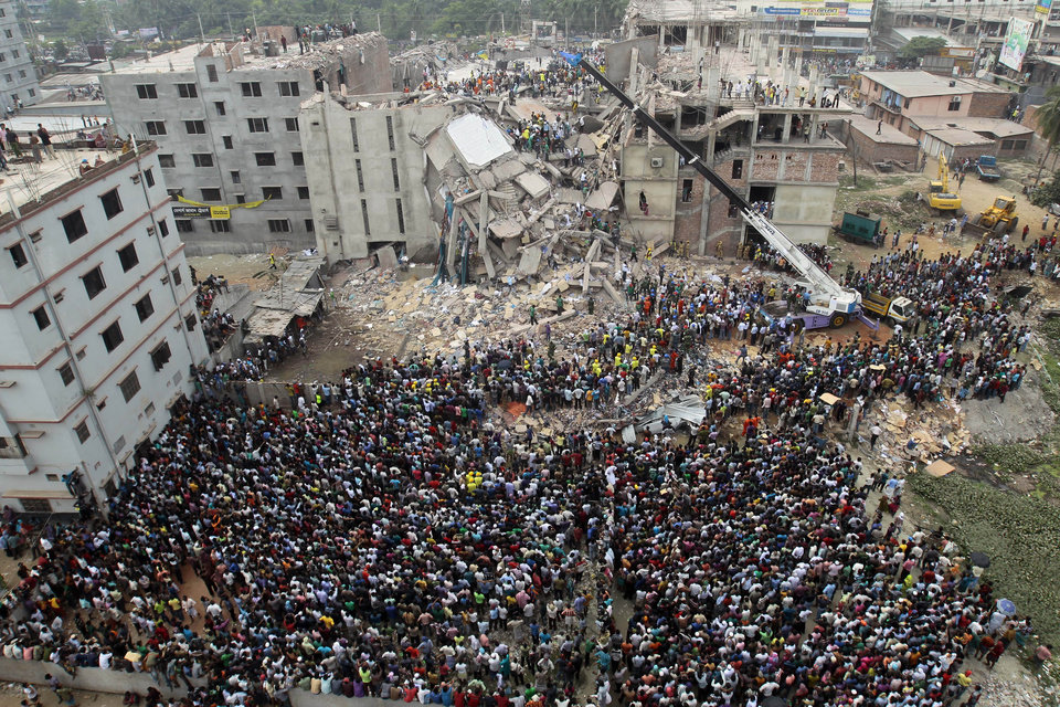 Photo - Bangladeshi people gather as rescuers look for survivors and victims at the site of a building that collapsed Wednesday in Savar, near Dhaka, Bangladesh,Thursday, April 25, 2013. By Thursday, the death toll reached at least 194 people as rescuers continued to search for injured and missing, after a huge section of an eight-story building that housed several garment factories splintered into a pile of concrete.  (AP Photo/A.M.Ahad)