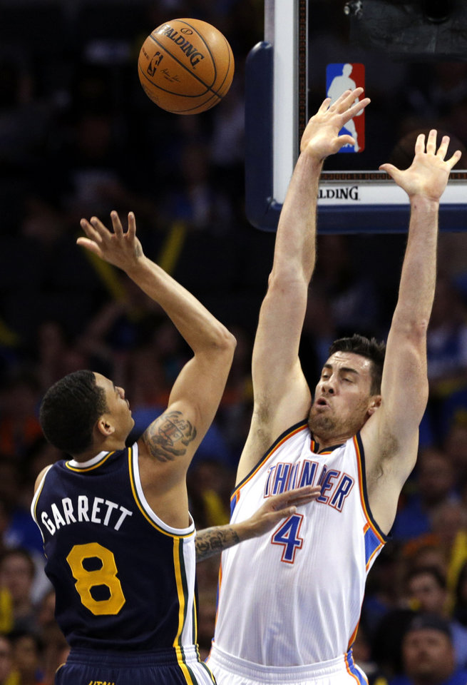 Photo - Oklahoma City 's Nick Collison (4) defends against Utah's Diante Garrett (8) during the NBA game between the Oklahoma City Thunder and the Utah Jazz at the Chesapeake Energy Arena, Sunday, March 30, 2014, in Oklahoma City. Photo by Sarah Phipps, The Oklahoman