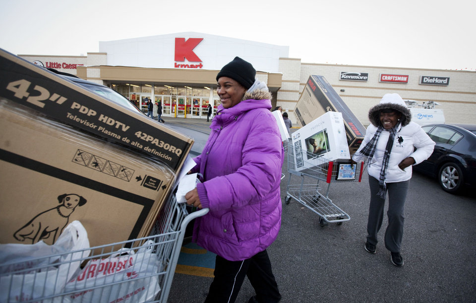 Photo -   IMAGE DISTRIBUTED FOR KMART - Customers Soalina Agers, left, and Val Gray, both from Chicago, walk through the Kmart parking lot with their pre-Black Friday deals at the Addison Street store in Chicago on Thanksgiving Thursday, Nov. 22, 2012. Kmart was the first major retailer nationwide to kick off pre-Black Friday shopping on Thanksgiving morning at 6 a.m. (John Konstantaras/AP Images for Kmart)