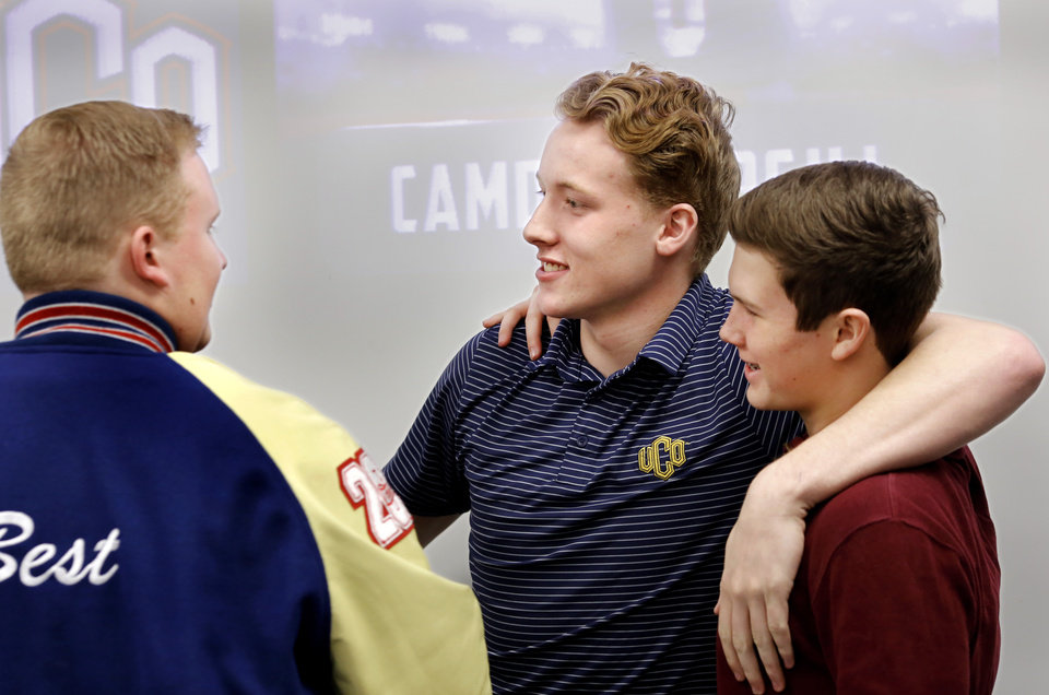 Photo - Camden Cargill, center,  greets and shares hugs with classmates and fellow team members after he signed his letter with UCO. Cargill is one of the many local kids signing a National Letter of Intent on Wednesday, Feb. 7, 2018, but as much as his decision to sign with UCO is about football, it's also about family. He could've gone to a bigger school. He could've gone to an Ivy League program, even. But he's staying closer to home because of his five new brothers and sisters, all under the age of 10 and all adopted within the past year from Africa.   Photo by Jim Beckel, The Oklahoman