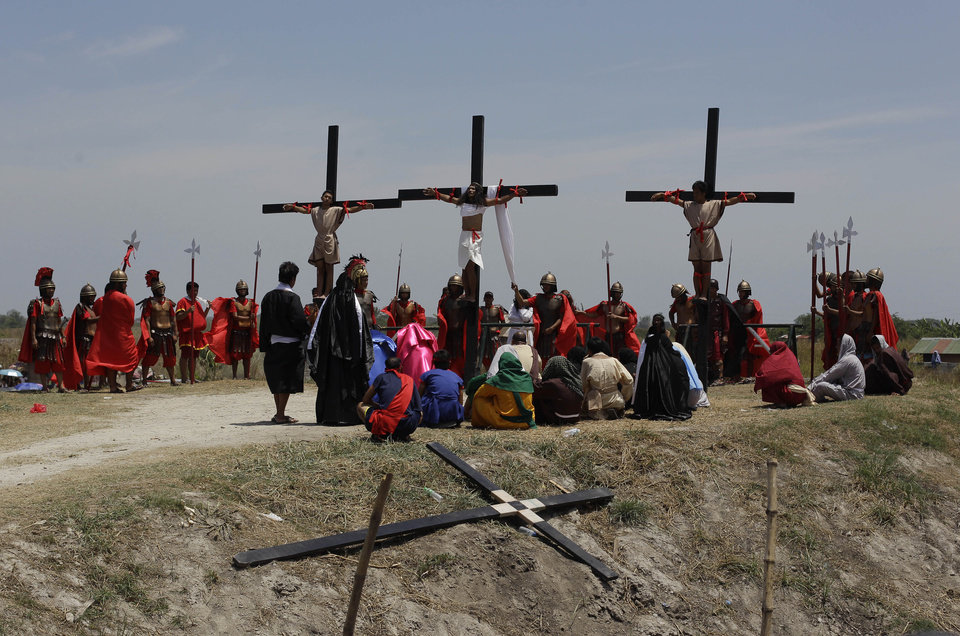 Photo - Filipino devotee Ruben Enaje, center, stays nailed to a cross with two actors during a play to re-enact the crucifixion of Jesus Christ in San Pedro Cutud village, Pampanga province, northern Philippines on Friday, April 18, 2014. Church leaders and health officials have spoken against the practice which mixes Roman Catholic devotion with folk belief, but the annual rites continue to draw participants and huge crowds. (AP Photo/Aaron Favila)