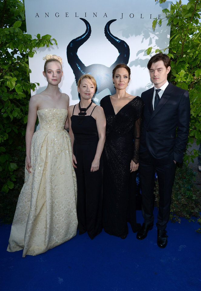 Photo - From left, actors Elle Fanning, Leslie Manville, Angelina Jolie and Sam Riley arrive for the Maleficent exhibit in Kensington Gardens, London, Thursday, May 8, 2014. The exhibit showcases some of the costumes and props from the film Maleficent, before they go on display to the public at the O2 in London.  (Photo by Jon Furniss/Invision for/AP Images)
