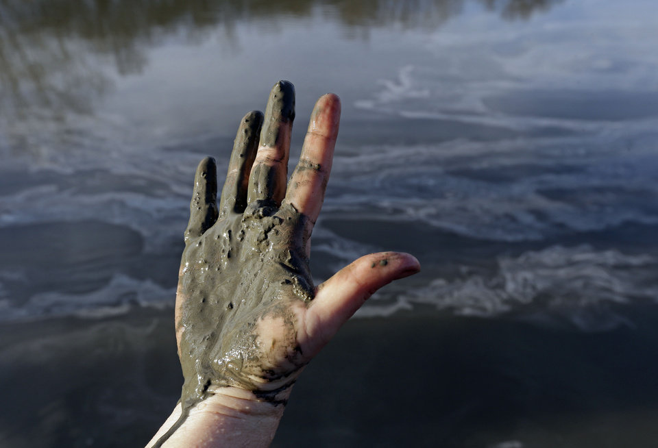 Photo - Amy Adams, North Carolina campaign coordinator with Appalachian Voices, shows her hand covered with wet coal ash from the Dan River swirling in the background as state and federal environmental officials continued their investigations of a spill of coal ash into the river in Danville, Va., Wednesday, Feb. 5, 2014. Duke Energy estimates that up to 82,000 tons of ash has been released from a break in a 48-inch storm water pipe at the Dan River Power Plant in Eden N.C. on Sunday. (AP Photo/Gerry Broome)