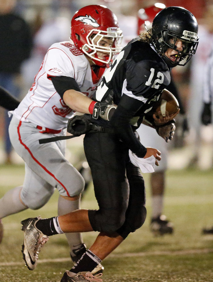 Josh Irvin (12) of Pond Creek-Hunter tries to break away from Fox's Jerry Mitchell (58) during a Class B semifinal high school football playoff game between Pond Creek-Hunter and Fox in Del City, Friday, Nov. 23, 2012. Photo by Nate Billings, The Oklahoman