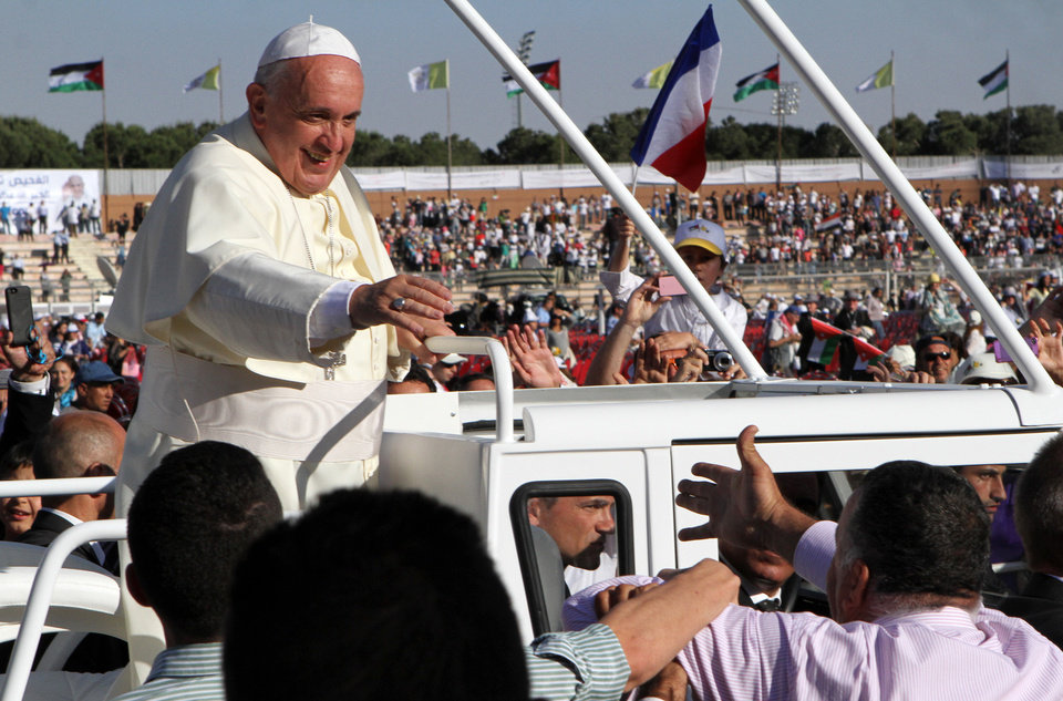 Photo - A man extends his arm toward Pope Francis after his arrival at Amman's international stadium in Jordan, Saturday, May 24, 2014. Pope Francis called on Saturday for an
