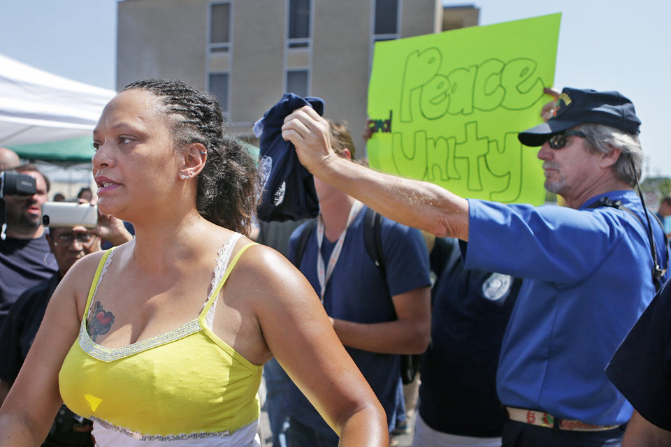 Photo - Sondra Fifer, of St. Louis, voices her disagreement with the rally for Ferguson police Officer Darren Wilson on Saturday, Aug. 23, 2014, at Barney's Sports Pub in St. Louis.