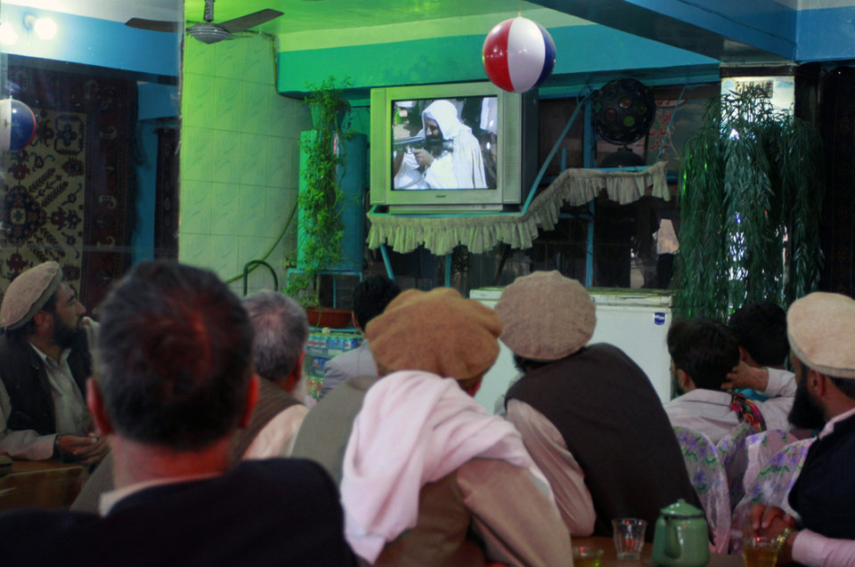 Photo - Afghan men watch television coverage announcing the killing of Al-Qaida leader Osama bin Laden at a local restaurant in Kabul, Afghanistan Monday, May 2, 2011. Bin Laden, the mastermind behind the Sept. 11, 2001, terror attacks that killed thousands of people was slain in his luxury hideout in Pakistan early Monday in a firefight with U.S. forces, ending a manhunt that spanned a frustrating decade. (AP Photo/Musadeq Sadeq)  ORG XMIT: XMS112