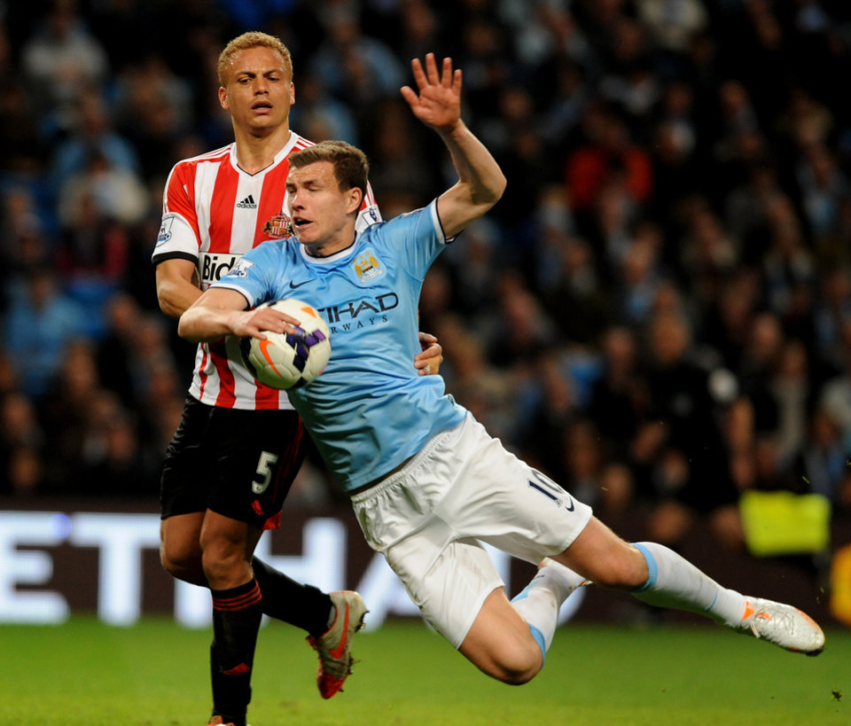Photo - Manchester City's Edin Dzeko is tackled by Sunderland's Wes Brown during the English Premier League soccer match between Manchester City and Sunderland at The Etihad Stadium, Manchester, England, Wednesday, April  16, 2014. (AP Photo/Rui Vieira)