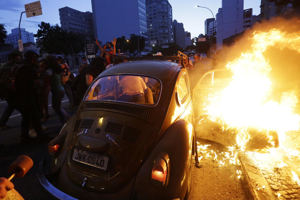 Photo - In this Saturday, Jan. 25, 2014 photo, a woman gets out of a car which caught fire when the driver tried to drive past a burning barricade set up by demonstrators demanding better public services, and protesting against the upcoming World Cup soccer tournament in Sao Paulo, Brazil. Last year, millions of people took to the streets across Brazil complaining of higher bus fares, poor public services and corruption while the country spends billions on the World Cup, which is scheduled to start in June. (AP Photo/Nelson Antoine)