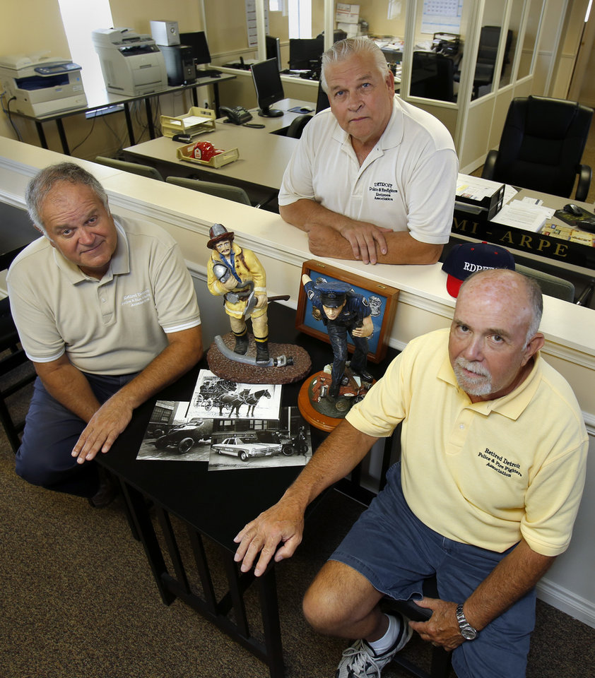 Retire Detroit Police Dept. officers Al Grant, left, Don Taylor and Greg Trozak, right, of the Retired Detroit Police and Fire Fighters Association, pose for a photo with some police and firefighter memorabilia at their office Friday, July 19, 2013 in Sterling Heights, Mich.