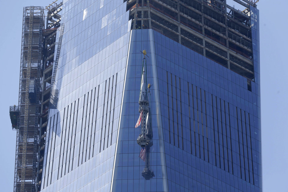 Photo - The top piece of the 408-foot spire for One World Trade Center is lifted to the top of the building in New York, Thursday, May 2, 2013. When it's fully installed, at a later date, it will top the building at a symbolic 1,776 feet.  (AP Photo/Seth Wenig)
