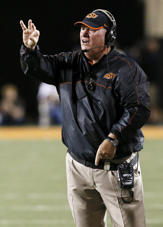 Photo - Oklahoma State defensive coordinator Bill Young gives instructions to the Cowboys during a college football game between Oklahoma State University (OSU) and West Virginia University (WVU) at Boone Pickens Stadium in Stillwater, Okla., Saturday, Nov. 10, 2012. OSU won, 55-34. Photo by Nate Billings, The Oklahoman