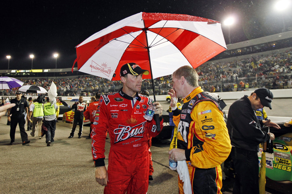 Photo -   Kevin Harvick, left, talks with Jeff Burton during a rain delay for the NASCAR Sprint Cup Series auto race at Richmond International Raceway in Richmond, Va., Saturday, Sept. 8, 2012. (AP Photo/Steve Helber)