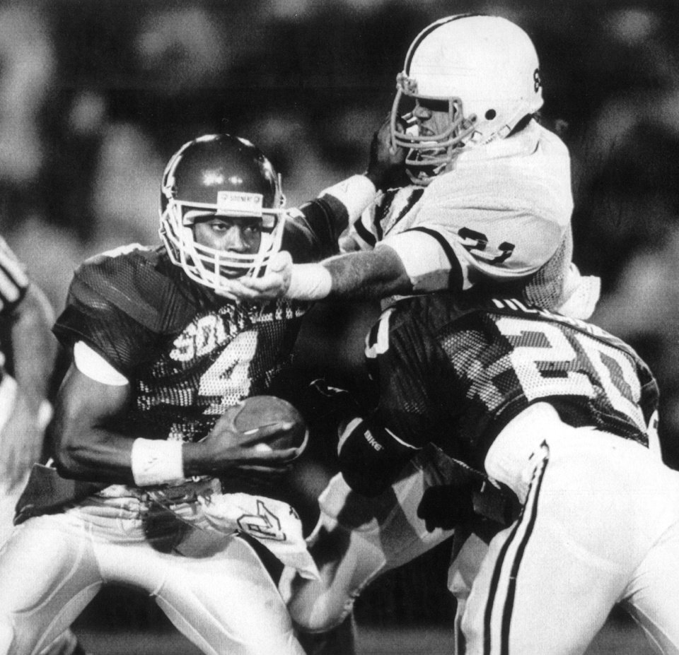 Photo - UNIVERSITY OF OKLAHOMA, COLLEGE FOOTBALL, OU SOONERS. 01/01/1986. Oklahoma quarterback Jamelle Holieway tries to evade Penn State's Sid Lewis (21) with an assist from OU running back Spencer Tillman (20) in the Orange Bowl.  Staff photo by Doug Hoke taken 1/1/86; photo ran in the 1/2/86 Daily Oklahoman. File:  Football/OU/OU-Penn State/Orange Bowl/Jamelle Holieway/1986