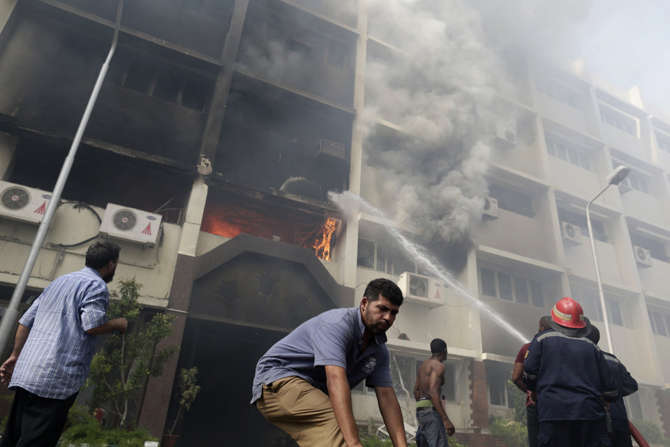 Photo - Egyptian firefighters battle flames at the Giza governorate building that was stormed and torched by angry supporters of Egypt's ousted president, Cairo, Egypt, Thursday, Aug. 15, 2013. Egypt faced a new phase of uncertainty on Thursday after the bloodiest day since its Arab Spring began, with hundreds of people reported killed and thousands injured as police smashed two protest camps of supporters of the deposed Islamist president. Wednesday's raids touched off day-long street violence that prompted the military-backed interim leaders to impose a state of emergency and curfew, and drew widespread condemnation from the Muslim world and the West, including the United States. (AP Photo/Hassan Ammar)