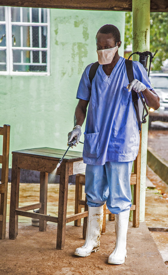 Photo - In this photo taken Saturday, Aug. 9, 2014,  a health worker wearing a protective clothing spray disinfectant against the deadly Ebola virus at the Kenema Government Hospital in Kenema, 300 kilometers, (186 miles) from the capital city of Freetown, Sierra Leone.  Over the decades, Ebola cases have been confirmed in 10 African countries, including Congo where the disease was first reported in 1976. But until this year, Ebola had never come to West Africa.  (AP Photo/ Michael Duff)