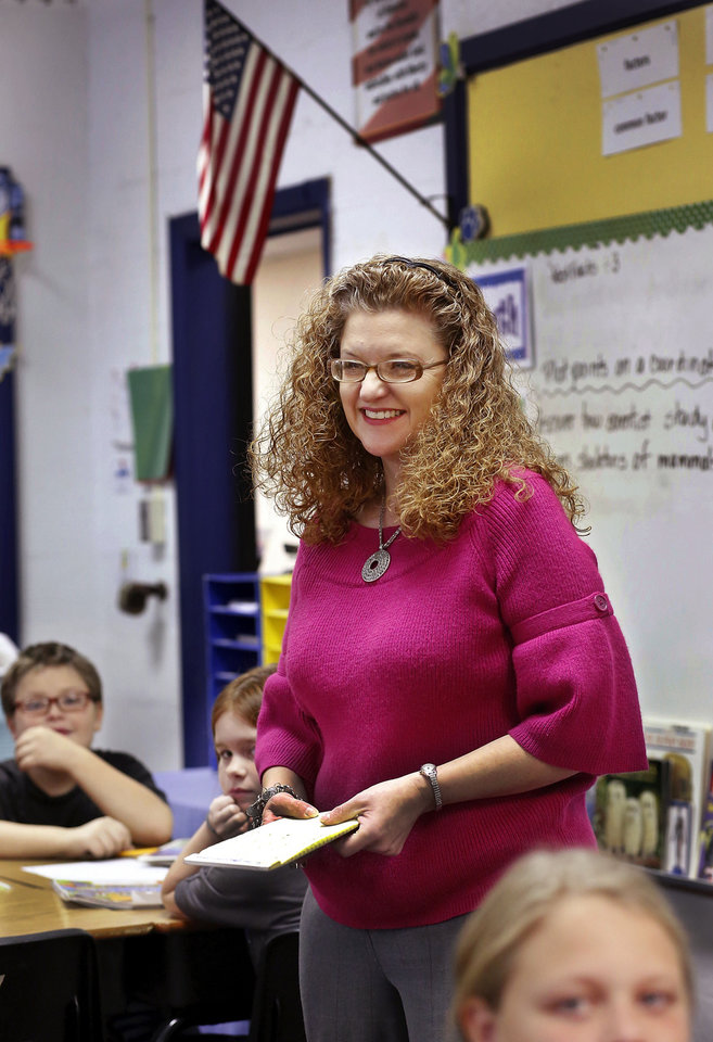 Photo - Sallie Harrison,  a fourth-grade science and math teacher at Meeker Elementary School, teaches a lesson in long division to her students. Harrison has has multiple sclerosis.    Photo by Jim Beckel, The Oklahoman  Jim Beckel - THE OKLAHOMAN