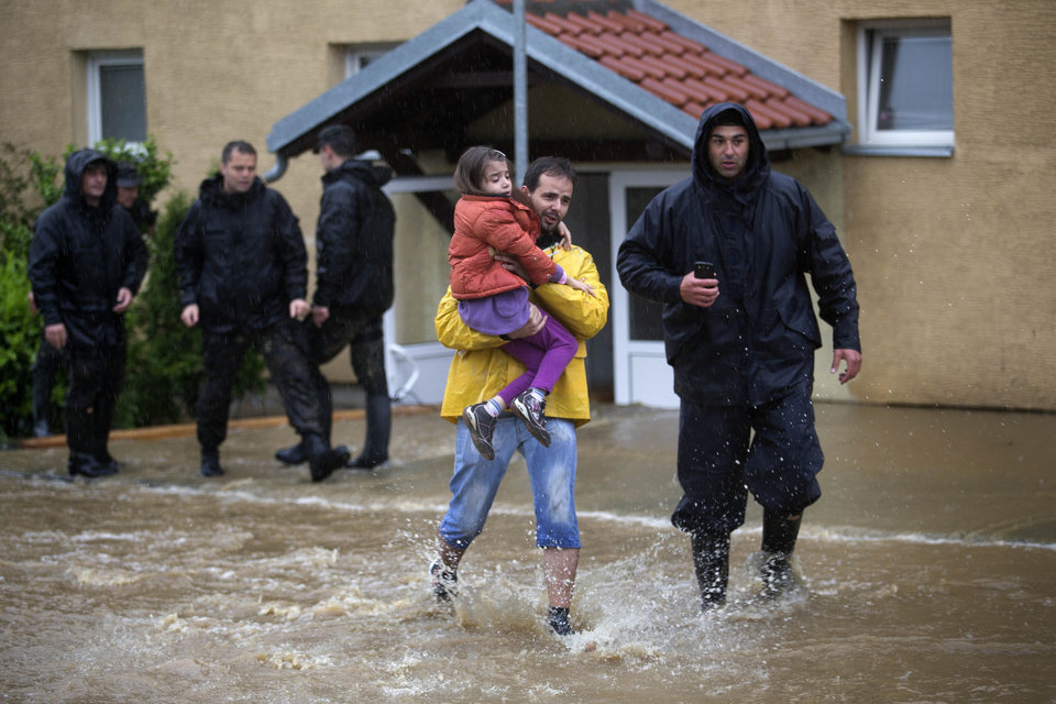 Photo - A man evacuates his daughter from their home hit by flood waters as police officers help out in a suburb of Belgrade, Serbia, Thursday, May 15, 2014. Some hundreds of people have been evacuated from their homes as floods caused by heavy rains gripped the Balkans Thursday, overflowing roads, bridges and railways, closing down schools, and cutting off power supplies and phone lines. (AP Photo/Marko Drobnjakovic)