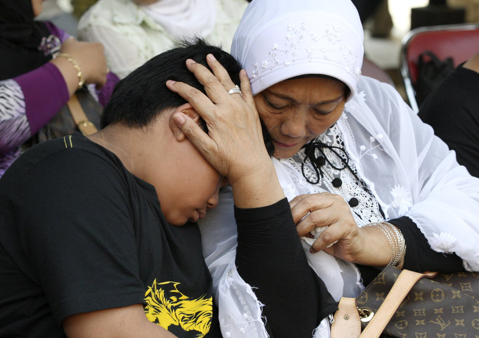 Photo -   An Indonesian woman comforts his grandson whose father was on board of the Russian-made plane that crashed into a mountain in West Java, as they wait for the identification process of the victims at the main police hospital in Jakarta, Indonesia, Saturday, May 12, 2012. Search teams were struggling to retrieve the bodies of the 45 people who were aboard the Sukhoi Superjet-100 that crashed on Wednesday during a demonstration flight for potential buyers. (AP Photo/Dita Alangkara)