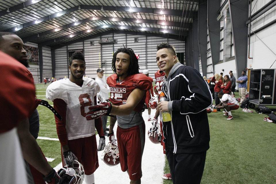 New Orleans Saints wide receiver Kenny Stills, right, talks with Oklahoma defensive back Zack Sanchez (15) and Oklahoma wide receiver Jalen Saunders (8) at the New Orleans Saints practice facility in Metairie, La., Saturday, Dec. 28, 2013.  Oklahoma will play Alabama in the Sugar Bowl on Jan. 2, 2014. (AP Photo/Bill Haber)
