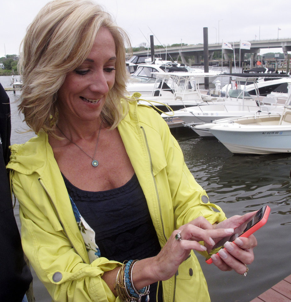 Photo - In this photo taken on May 28, 2014, Helen Henderson, a project manager for the American Littoral Society, demonstrates a new smart phone app developed for the group that lets people quickly and easily report water pollution or other marine environmental problems to authorities at a marina in Brick, N.J. The project was paid for by a $325,000 federal grant that came from fines levied on water polluters. (AP Photo/Wayne Parry)