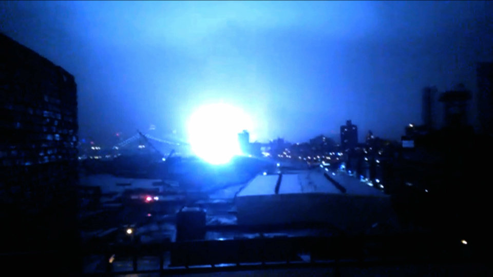Photo -   This image from video provided by Dani Hart shows what appears to be a transformer exploding in lower Manhattan as seen from a building rooftop from the Navy Yard in Brooklyn during Sandy's arrival in New York City. Much of New York was plunged into darkness Monday by a superstorm that overflowed the city's historic waterfront, flooded the financial district and subway tunnels and cut power to nearly a million people. (AP Photo/Dani Hart)