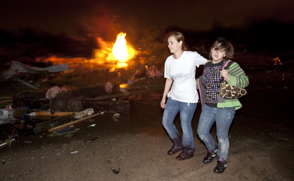 Photo -   Two people walk past a gas fire in the Pinaire mobile home park in Wichita, Kansas Saturday April 14, 2012 after a tornado caused massive destruction in the area on Saturday night. Tornadoes were spotted across the Midwest and Plains on Saturday as an outbreak of unusually strong weather seized the region, and forecasters sternly warned that