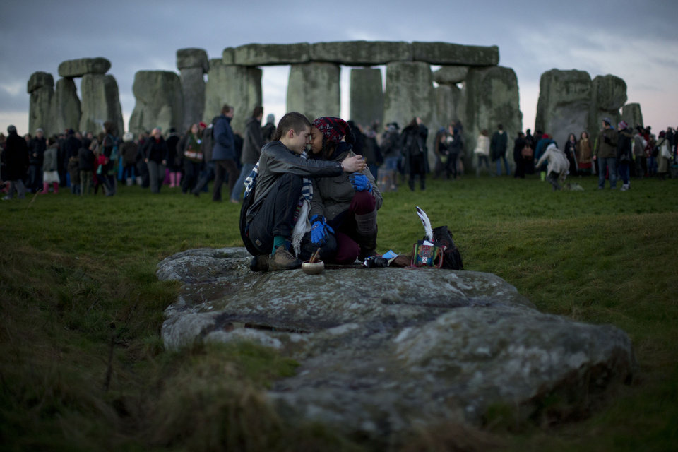 "People embrace by the ancient stone circle of Stonehenge, in southern England, as access to the site is given to druids, New Age followers and members of the public on the annual Winter Solstice, Friday, Dec. 21, 2012. Doomsday hour is here and so still are we. According to legend, the ancient Mayans' long-count calendar ends at midnight Thursday, ushering in the end of the world. Didn't happen. ""This is not the end of the world. This is the beginning of the new world,"" Star Johnsen-Moser, an American seer, said at a gathering of hundreds of spiritualists at a convention center in the Yucatan city of Merida, an hour and a half from the Mayan ruins at Chichen Itza. (AP Photo/Matt Dunham)"