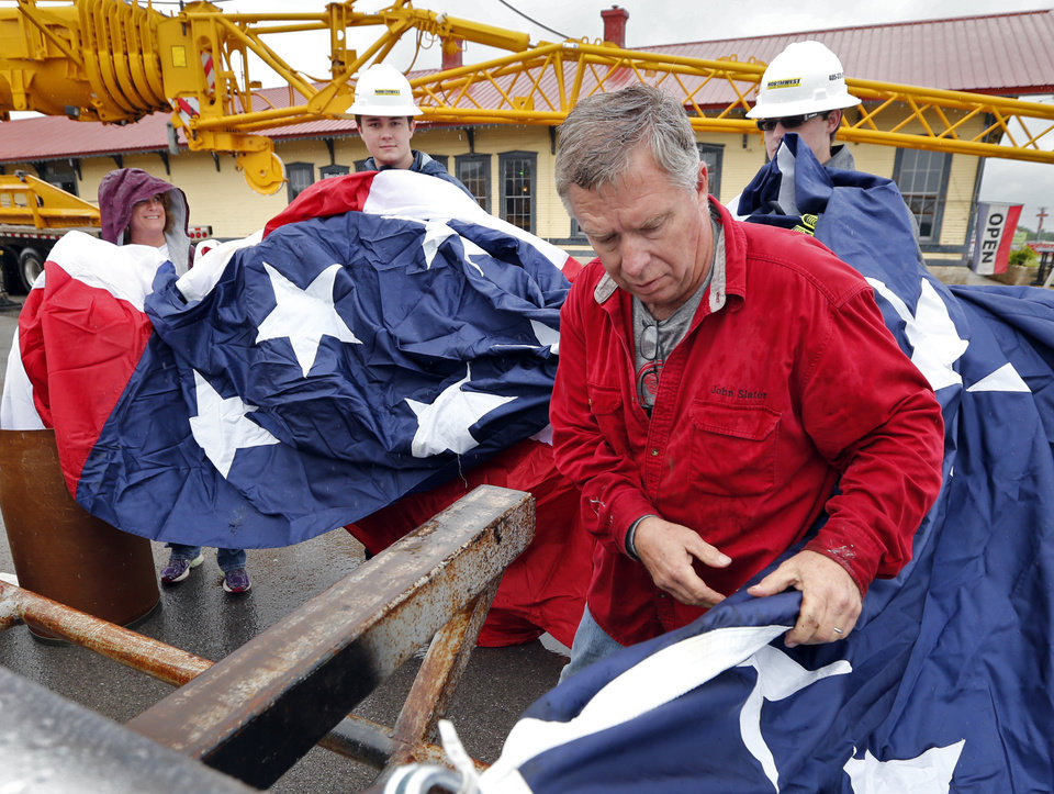 Photo - Above:  John Slater gets ready to hoist a giant flag in downtown Davis.  STEVE SISNEY -